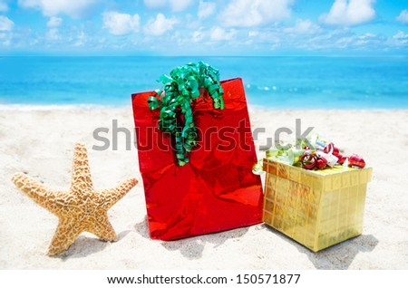 Starfish with gift box and bag on sandy beach in sunny day- holiday concept
