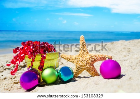 Starfish with gift box and christmas balls on the beach by the ocean - holiday concept