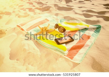 Starfish with sunglasses and mobile phone kept on beach blanket against orange and blue sky with clouds #531925807