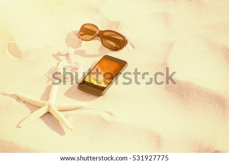 Starfish with sunglasses and mobile phone kept on sand against landscape with sunset #531927775
