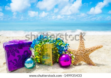 Starfish with two gift boxes and Christmas balls on sandy beach in sunny day- holiday concept