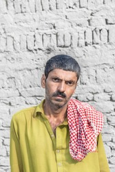 staring poor farmer in a village looks so worried or sad