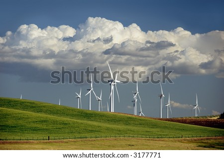 Stark White Electrical Power Generating Windmills on Rolling Hills, Beneath Summer Cumulus Clouds
