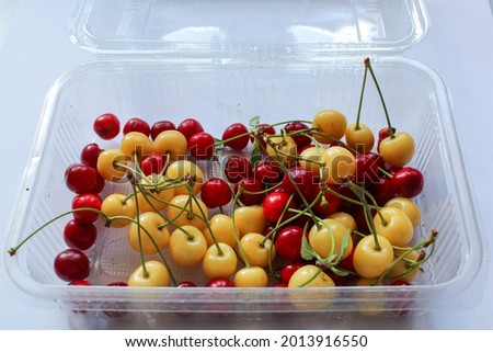 Starks Gold cherries and red cherries on a white background. Photo of organic yellow and red cherries. Many cherries in transparent container. Stock photo ©