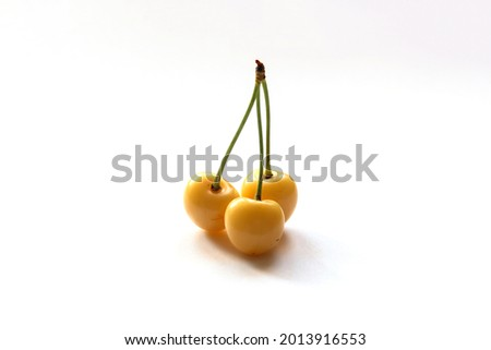 Starks Gold cherry on a white background. Three yellow cherries. Selective focus. Stock photo ©