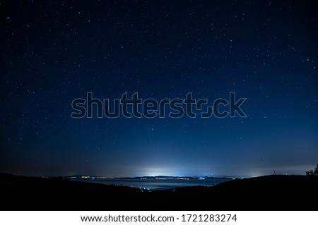 Starry night sky over city lights.
