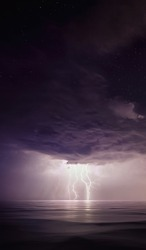 Starry night with Thunderstorm. Night thunderstorm with lightning above the sea