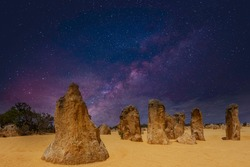 Starry sky above pillars of fossil plant remains The Pinnacles in Nambung National Park in Western Australia with golden yellow ornaments on the foreground against the sky of the Milky Way galaxy