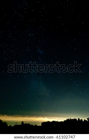 starry sky. clouds at the horizon lighting from the lights from a city. contours are visible from a wood.
