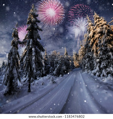 starry sky in winter snowy night. fantastic milky way in the New Year's Eve. Winter road in the mountains. fireworks and holiday lights on the background. Photo greeting card.