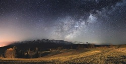 Starry sky over mountains. Bright milky way above mountains. Gorgeous night landscape.