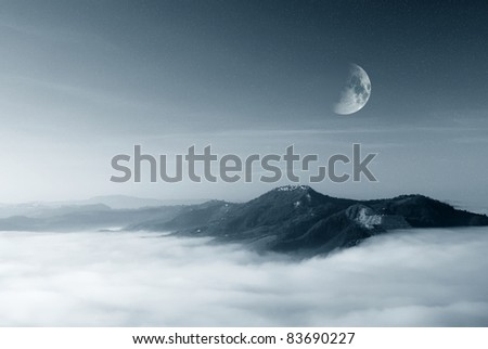 starry sky with moon over the foggy valley