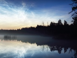Starry sky with noctilucent clouds and fog above the Saimaa lake, Finland, at summer solstice night. Long exposure. Symmetry reflections, natural mirror. Mystic landscape, pagan celebration
