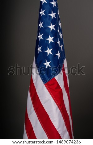 Starry striped flag of the United States of America hanging on a flagpole on a dark background #1489074236