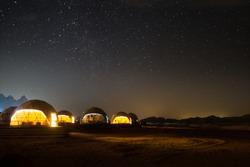 Stars above martian dome tents in Wadi Rum Desert, Jordan.