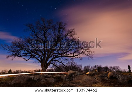 Stars and clouds move through the sky behind a tree at night near Devil's Den, Gettysburg, PA - stock photo