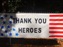 Stars and Stripes banner thanking the military and first responder heroes hanging from a fence