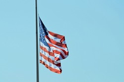 Stars and stripes flag fluttering in the breeze, tethered on the left hand side, and set against a bright blue background.
