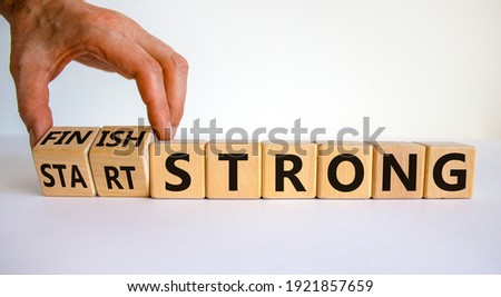 Start and finish strong symbol. Businessman turns wooden cubes, changes words 'start strong' to 'finish strong'. Beautiful white background, copy space. Business and start and finish strong concept.