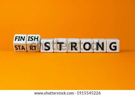 Start and finish strong symbol. Turned wooden cubes, changed words 'start strong' to 'finish strong'. Beautiful orange background, copy space. Business and start and finish strong concept.