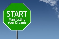 Start Manifesting Your Dreams text on green stop sign with blue sky background and copy space