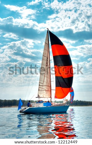 Start of a sailing regatta, fully crewed yacht with black and red sails catching the wind, blue sky and white clouds on background.