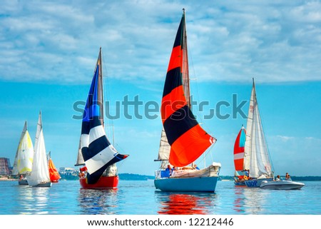 Start of a sailing regatta, fully crewed yachts with sails catching the wind, blue sky and white clouds on background.