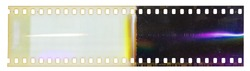 Start of 35mm negative filmstrip, first frame on white background, real scan of film material with cool rainbow scanning light interferences on the material.