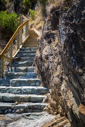 Start of the long steep staircase with stone steps at the coast by the coastal wall, Abel Tasman National Park New Zealand