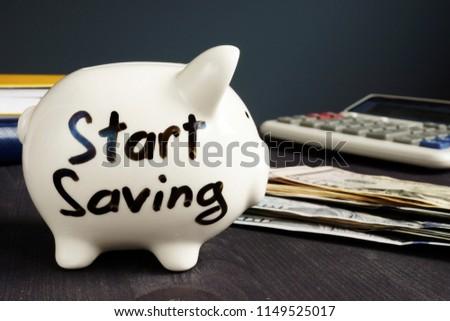 Start Saving written on a piggy bank and money.
