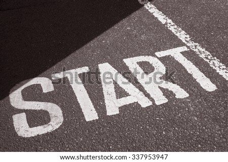 Start Sign on Paved Surface in Black and White Sepia Tone #337953947