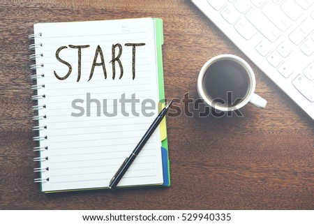 Start  text on notebook with coffee and keyboard on table #529940335