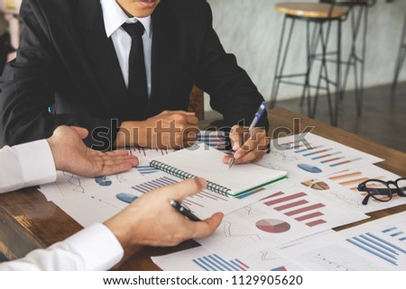 Start up business. people team work meeting point to discuss the graph up and down of economy and work on table.Selective Focus #1129905620