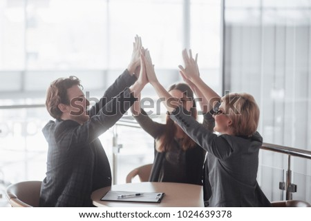 Start up concept. Group of young business partners giving high five at office.  #1024639378