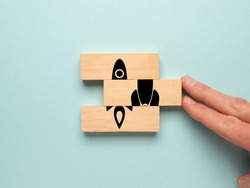 Start up concept with wooden blocks on a blue background, Hand of a businessman pushes wooden blocks together