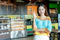 Start up of enterprise. Successful small business owner standing standing at front counter Coffee Shop of her. Asian woman leader the Franchise or new business self-confident with copy space for text