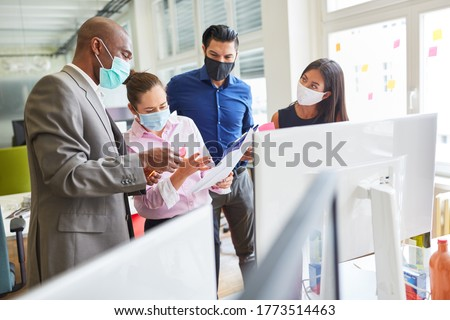 Start-up team colleagues with face mask in a project meeting in the internet agency