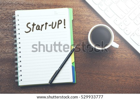 Start-up text on notebook with coffee and keyboard on table #529933777