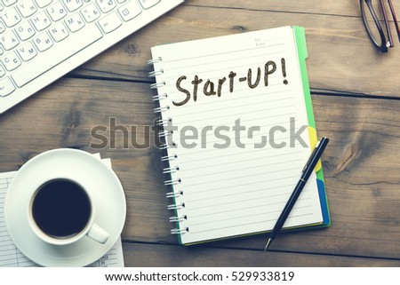 Start-up text on notebook with coffee and keyboard on table #529933819