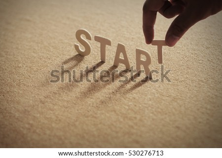 START wood word on compressed board with human's finger at T letter #530276713