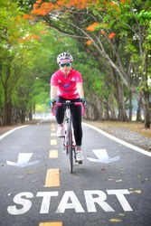 Start word on road with sportswoman ride bike on countryside with tree tunnel, healthy lifestyle concept and keep moving idea