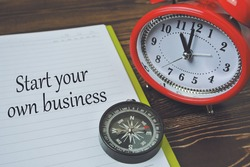 Start Your Own Business wording on note book, inscription with compass and red watch. Business and education concept.