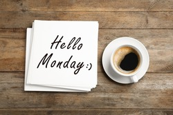 Start your week with good mood. Paper sheets with text Hello Monday and cup of coffee on wooden table, flat lay