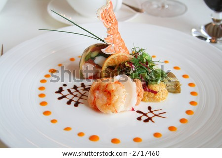 Starter or Entree of a french dish with seafood mixed among salad leaves.