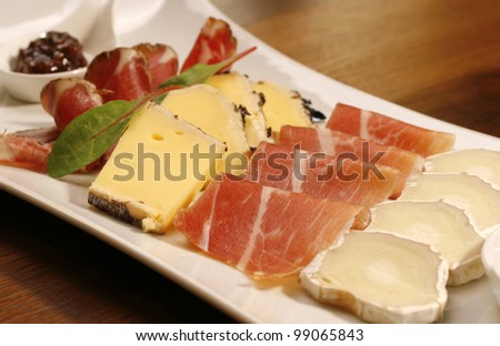 Starter plate (cheese and ham) on brown wood table (horizontal).