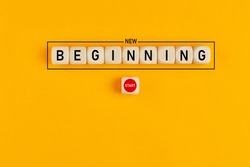 Starting a new beginning concept. The word new beginning on wooden cubes with a start button on yellow background.