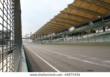 Starting & finishing point  of a race track with patron grandstand alongside. Concept of spectatorship for decisive sport moments.