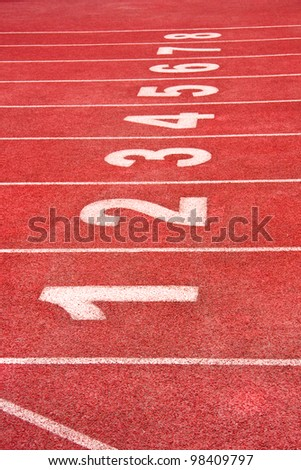 starting line on a red running track - stock photo