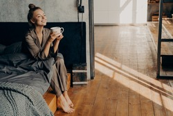 Starting new beautiful day. Cute pretty woman with cup of morning coffee chilling while sitting on bed, relaxing in brown satin pajama in modern apartment. Happy time at home