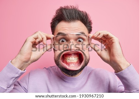 Startled handsome man stares surprisingly through transparent spectacles clenches teeth has widely opened mouth hears great news stands alarmed being super shocked stands indoor. Emotions concept Stockfoto ©